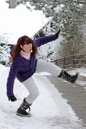 Dangerously slippery roads and sidewalks in winter. A woman slips on a snowy road