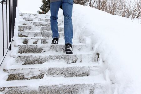 In winter it is dangerous to walk up a snow-covered staircase. A man walks up a staircase in winter Фото со стока - 134269856