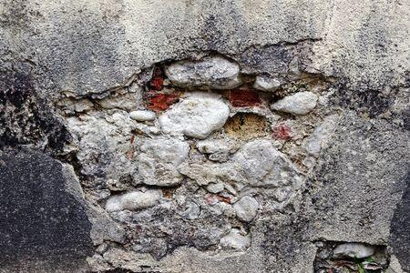 A broken, dilapidated stone wall. A damaged house wall Фото со стока
