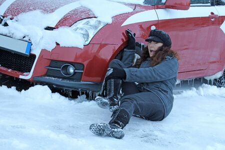A woman slips in winter and fell in front of a car. Danger in winter road traffic Фото со стока - 135613791