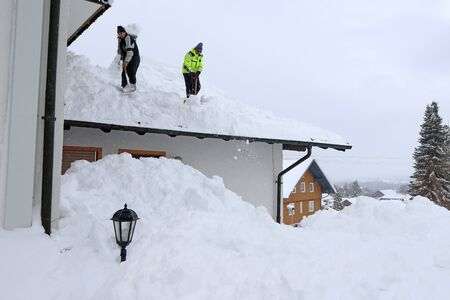 Two men shoveling high heavy snow from a house roof Фото со стока - 135615548