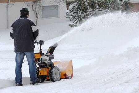 A man clears the road and the sidewalk with a snow blower Фото со стока
