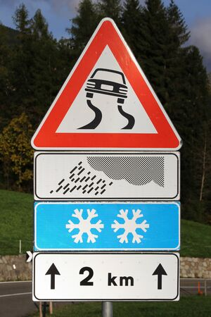 Road sign Attention Danger of slipping in rain and snow Фото со стока
