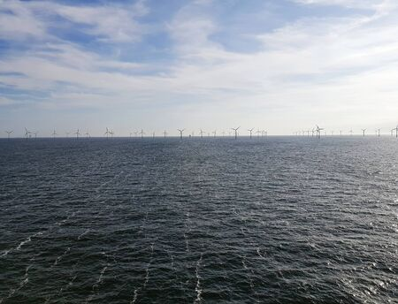 Offshore wind farm in the sea. Wind turbine in the water Фото со стока