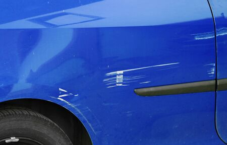 Scratches and dents on a blue car. Accidental damage to a car Фото со стока - 137297337