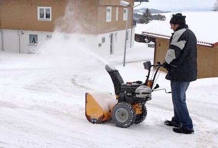 A man clears the road and the sidewalk with a snow blower Фото со стока - 137297438