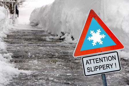 An icy road in winter with a sign Attention slippery!