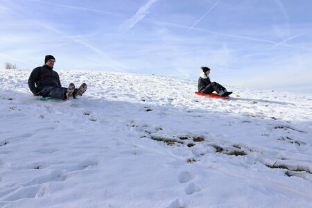 A woman and a man riding a snowmobile down a mountain in winter