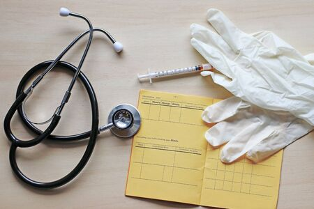 Vaccinations against measles, mumps and rubella with vaccination card, syringe and gloves