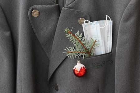 Corona and Christmas. A man suit with protective mask, fir branch and Christmas tree ball.