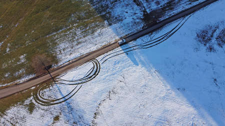 Drone photo of white car driving from light to shadow on road in winter Фото со стока
