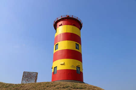 The red and yellow Pilsum lighthouse on the East Frisian North Sea coast in Germany