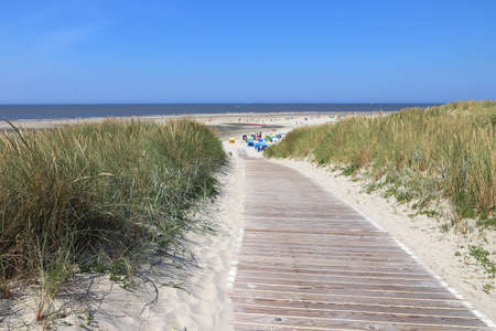 A path made of wood leads to the sandy beach on the North Sea island of Langeoog in Germany Фото со стока