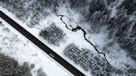 Aerial drone shot of a road with a car driving through the forest in winter