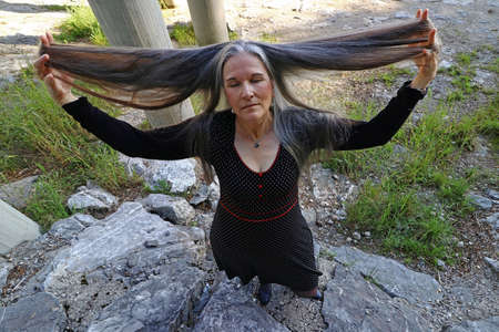 An older woman dreamily stretches her very long hair upwards