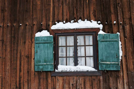 A window with green shutters on an old farmhouse in winter with snow Standard-Bild