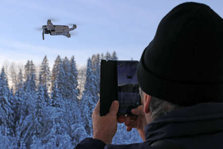A man takes a picture of a flying drone with his smartphone