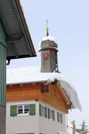 A dangerous roof avalanche on a house roof in front of a church in winter. Snowy church tower in Bavaria