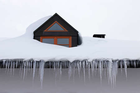 Large dangerous icicles and a roof avalanche on a house roof in winter