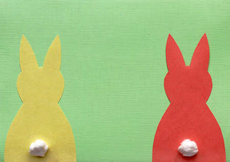 One yellow and one red paper Easter bunny on green background
