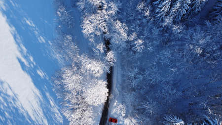 Aerial drone shot of street with snowy landscape and red car