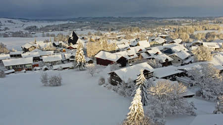 Aerial drone shot of a small town in Bavaria with snow in the evening sun Standard-Bild