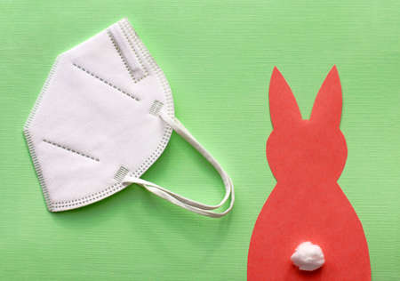 FFP2 protective mask and a red paper Easter bunny on a green background.