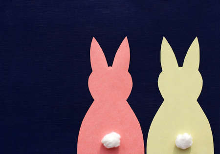 One yellow and one red paper Easter bunny on a dark blue background