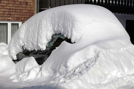 A snowed up black car in a parking lot in front of a house in winter Standard-Bild