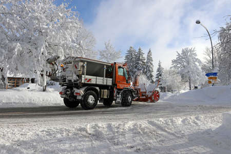 A snow plow with a snow blower drives through the street in winter to clear the high snow away