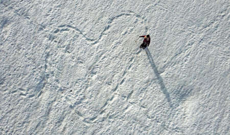 Aerial shot with a drone of a snow school runner making a trail in the shape of a heart in the snow