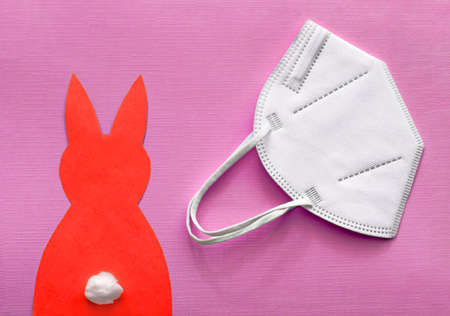 FFP2 protective mask and a red paper Easter bunny on a bright red background. Standard-Bild