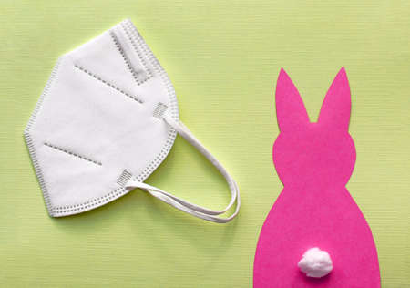 FFP2 protective mask and a pink paper Easter bunny on a yellow background.