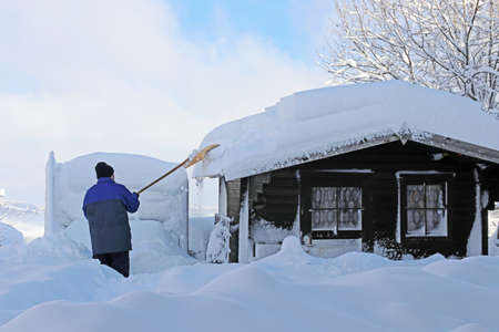 Man shovels high heavy snow from roof of wooden hut Standard-Bild