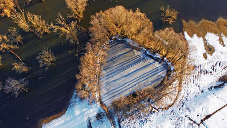 Aerial view from drone of small lake in heart shape with trees next to big lake in winter