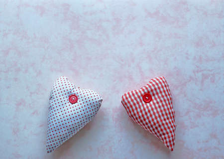 Two red and white fabric hearts on a pink marbled paper background