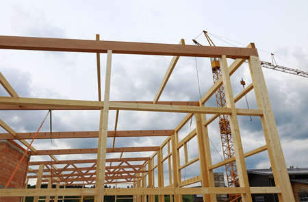 Wooden beams and crane at a construction site. The construction of a large wooden house. Standard-Bild