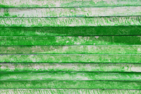 Many green and white wooden boards lie on a pile.