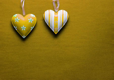 Two white and yellow metal hearts on a golden paper background