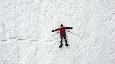 Aerial drone shot of woman snowshoeing lying in snow Standard-Bild