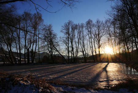 Winter sunset on frozen lake with light and shadow Standard-Bild