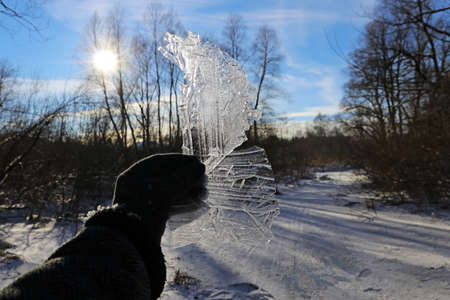A woman holds pieces of ice with pattern against the sun in winter