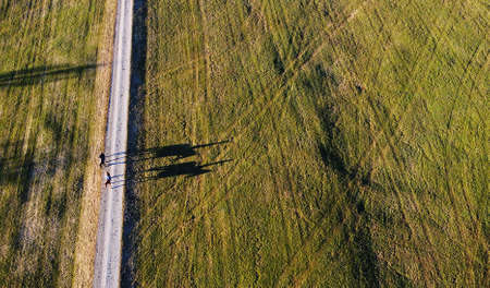 Aerial drone shot of two female riders on horses with a funny shadow