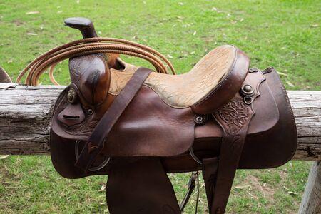 horse saddle: brown horse saddle on wood bar at farm