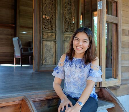 one girl: portrait of one Thai girl smiling at her wood home in evening