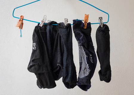 wet men: dirty socks on  clothes hanger by man who hurry