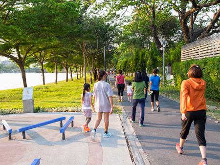 hacer footing: grupo de personas ruuning en el parque por la tarde