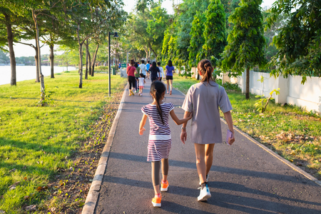 couple of mother and daughter running together in park in evening
