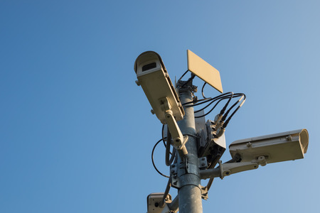 keep an eye on: closed up on installed cctv outdoor with sky and sunlight