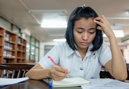 examination stress: selective focus on thai young adult woman student in uniform reading a book in library with stress Stock Photo